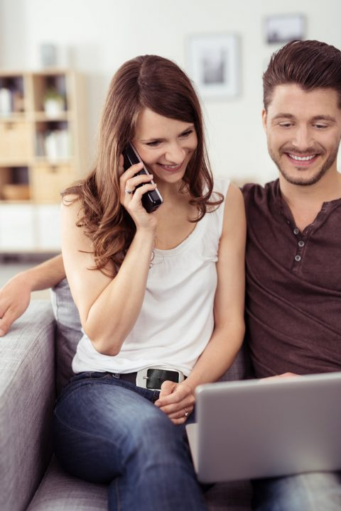 sweet couple on phone and laptop reviewing website