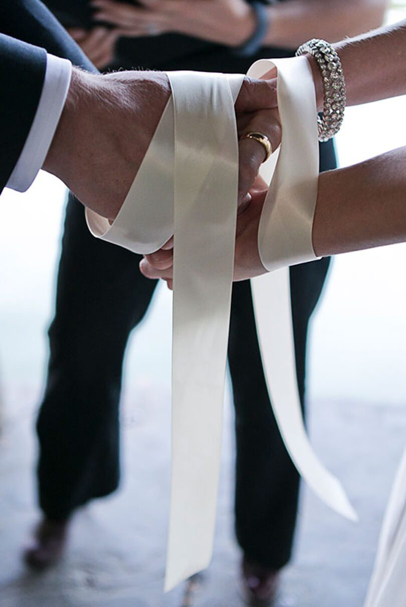 hand fassting ritual with white ribbon