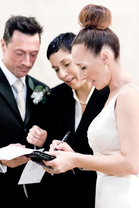 happy newlyweds signing their marriage license with their minister