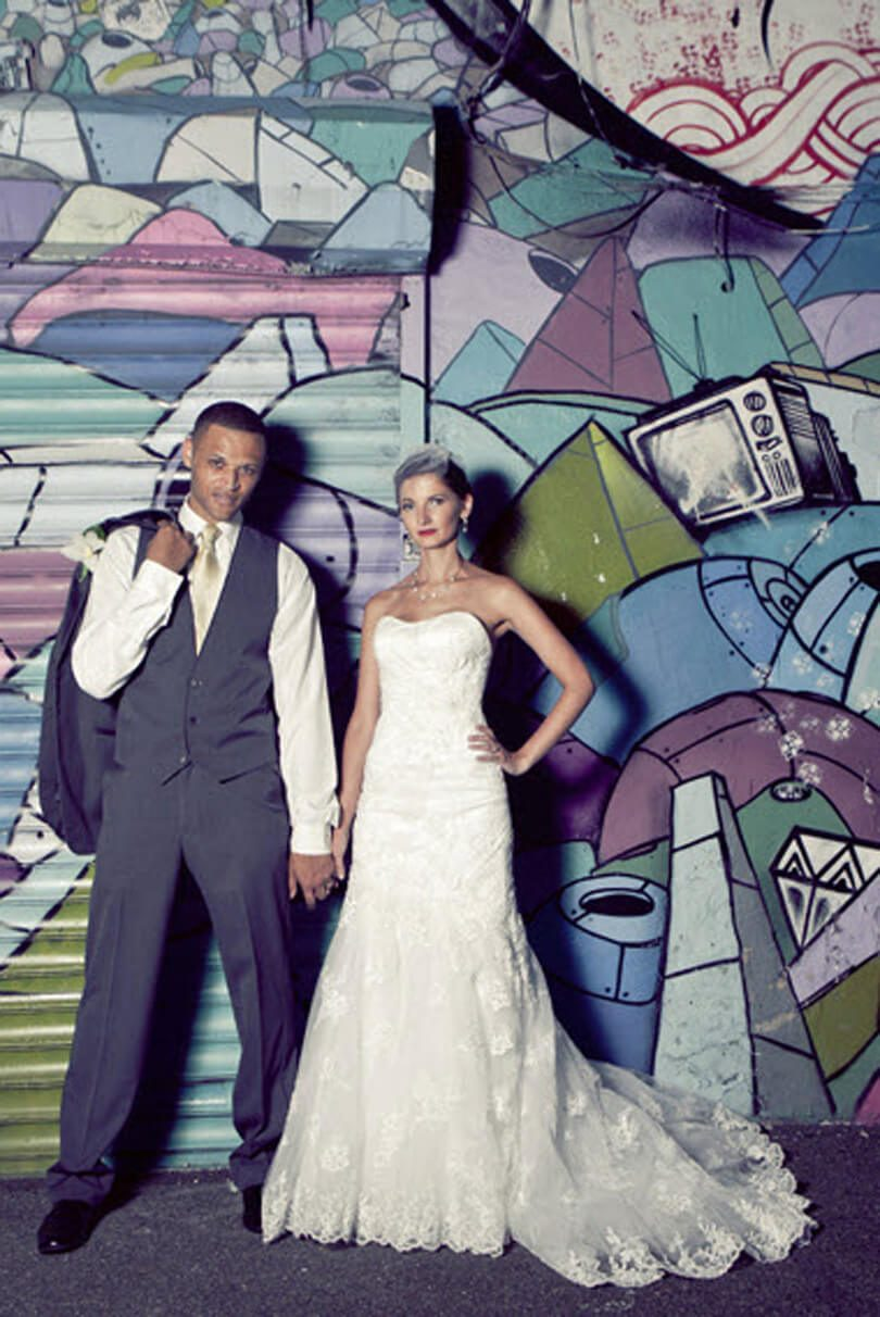 Modern interracial bride and groom in front of graffiti art